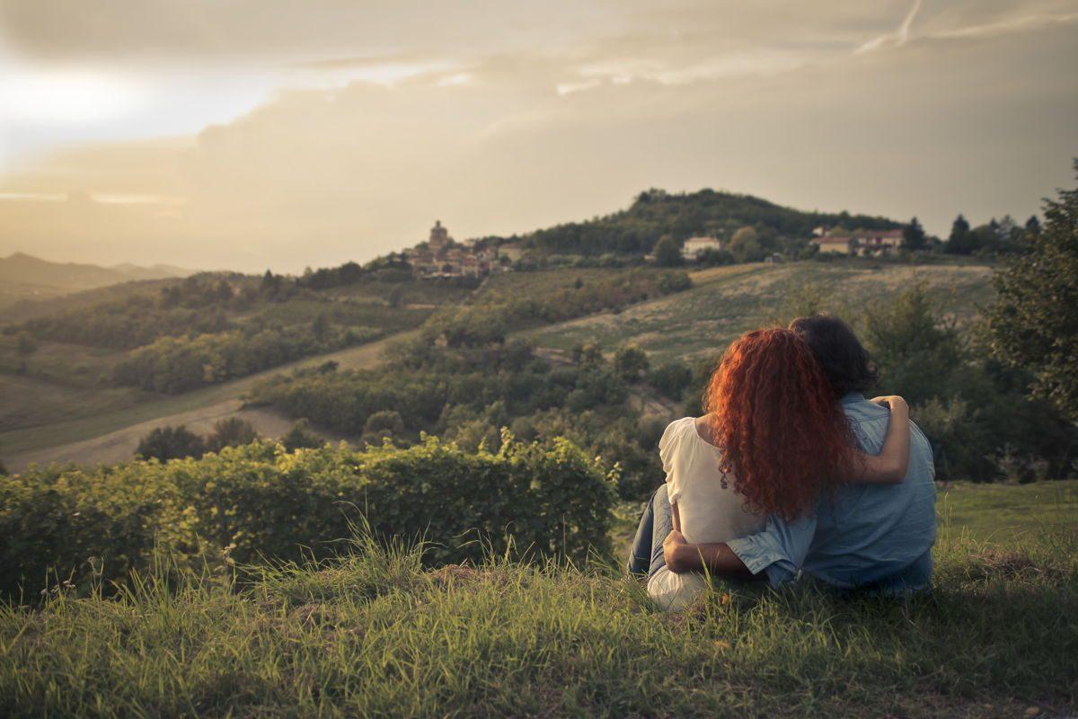Due ragazzi che guardano il territorio della Toscana durante il tramonto